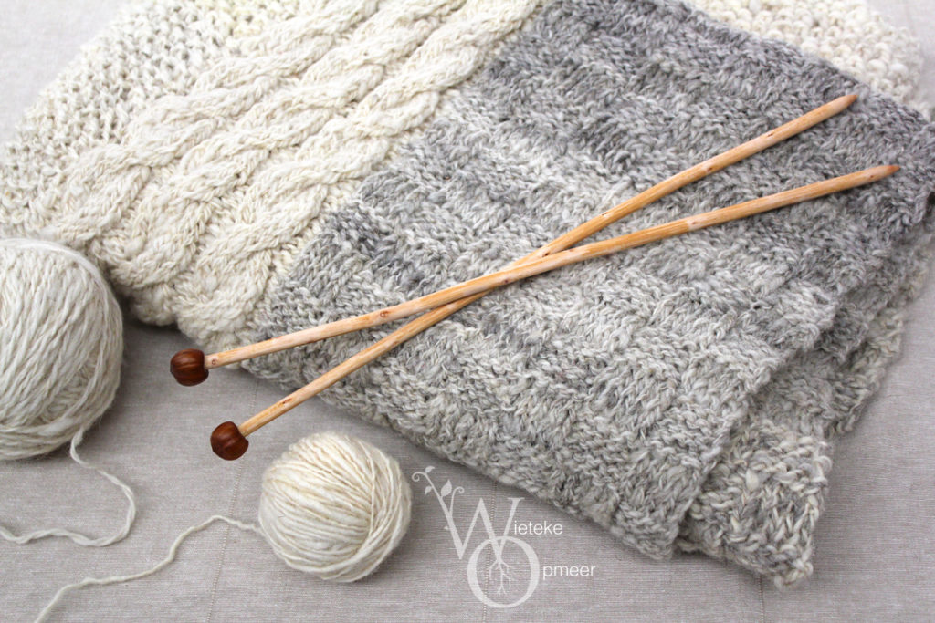 a set of wooden, hand carved organically shaped knitting needles with acorn ends