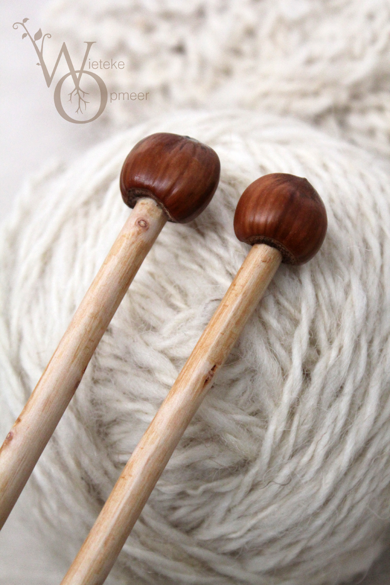 close-up of acorns ends of hand carved knitting needles