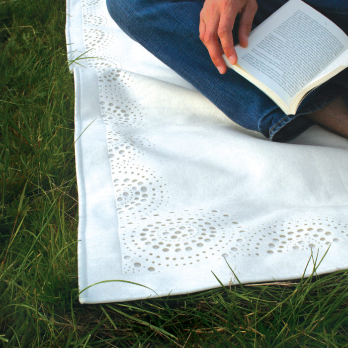 detail of white felt picnic rug in grass.