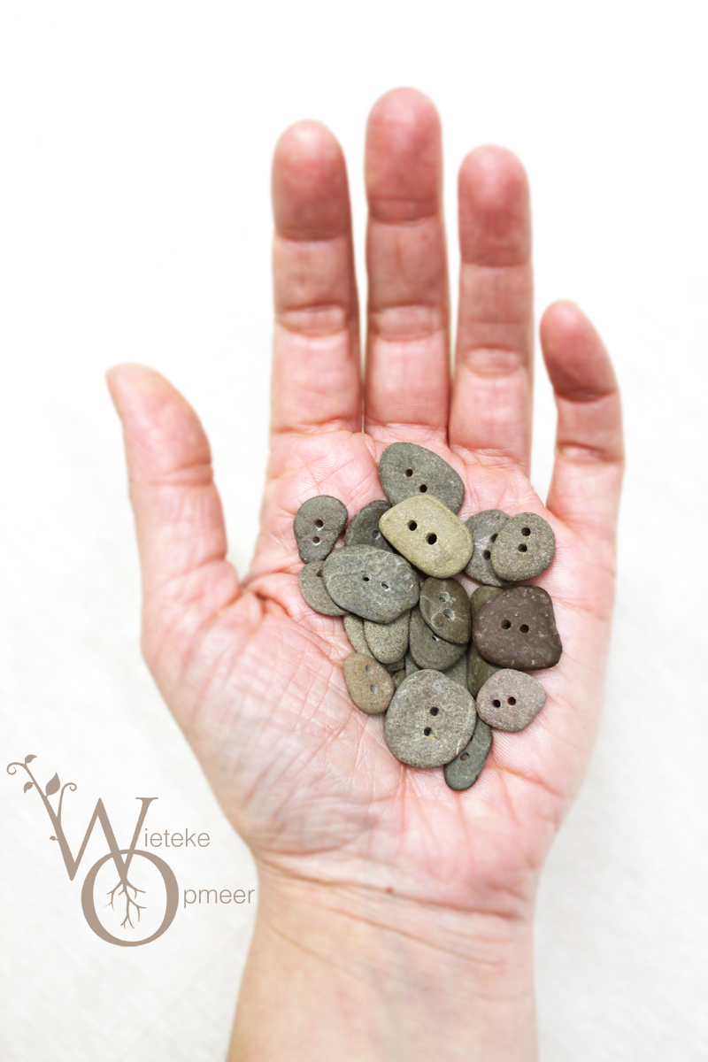 hand filled with various handmade riverstone buttons